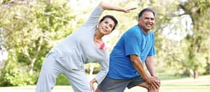 Elderly couple stretching in the park