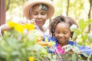 elder woman an kid watering plants